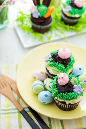 Easter chocolate cupcakes decorated with piggy and bunny ears. photo