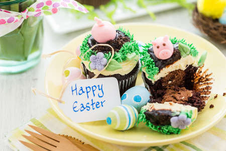 Easter chocolate cupcakes decorated with piggy and bunny ears. Stock Photo