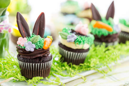 bunny ears: Easter chocolate cupcakes decorated with piggy and bunny ears. Stock Photo