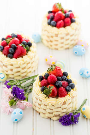 Easter basket mini cakes with glazed fresh fruit on top. photo