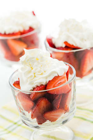 Fresh strawberries with whippes in glass bowls cream for dessert. photo