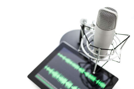 Studio microphone for recording podcasts and computer tablet on a white background. Archivio Fotografico