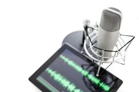 Microfoon van de studio voor het opnemen van podcasts en computer tablet op een witte achtergrond. Stockfoto