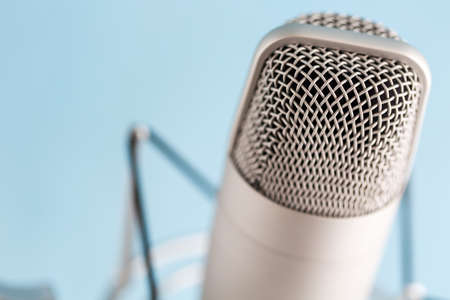 podcasting: Studio microphone for recording podcasts on a blue background.