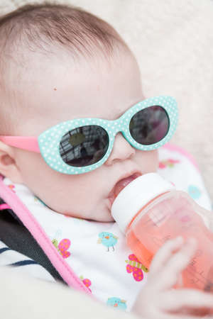 Cute baby girl wearing cute sunglasses in a car seat. photo