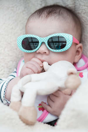 car seat: Cute baby girl wearing cute sunglasses in a car seat. Stock Photo