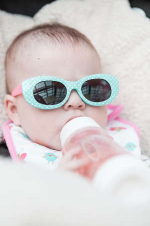 Cute baby girl wearing cute sunglasses in a car seat. photo