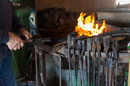 A blacksmith working at an old iron forge. Imagens