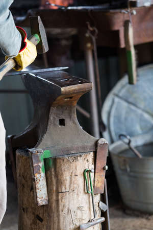 A blacksmith forging hot iron on the anvil.