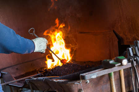 forge: A blacksmith working at an old iron forge. Stock Photo