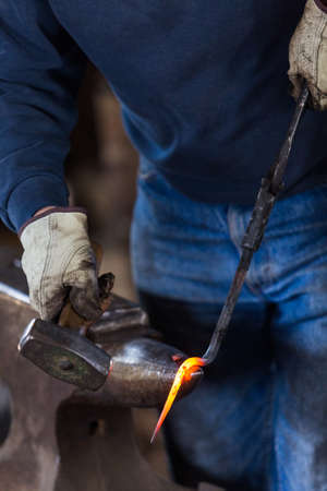 blacksmith bending hot iron on the anvil.