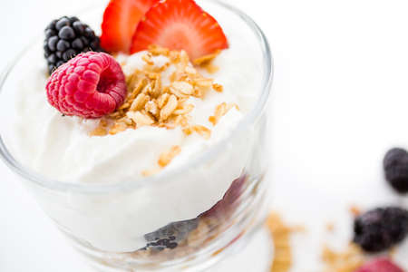 Breakfast parfait made from Greek yogurt and granola topped with fresh berries. photo
