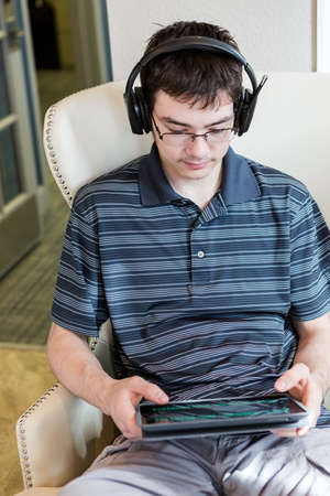 podcasting: Teenage boy playing with his computer gadgets at leisure time. Stock Photo