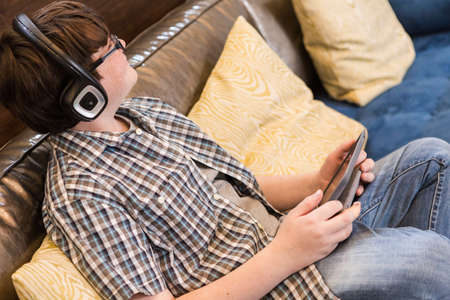 media gadget: Teenage boy playing with his computer gadgets at leisure time. Stock Photo