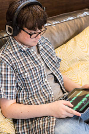 Teenage boy playing with his computer gadgets at leisure time. photo