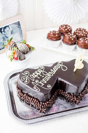 anniversaire mariage: C�l�bration d'anniversaire de mariage avec la forme de coeur g�teau au chocolat.