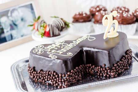 Celebrating wedding anniversary with heart shape chocolate cake.