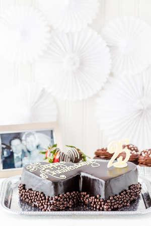 Celebrating wedding anniversary with heart shape chocolate cake. photo
