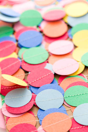 nad made: Making a colorful paper garland with reound puncher. Stock Photo