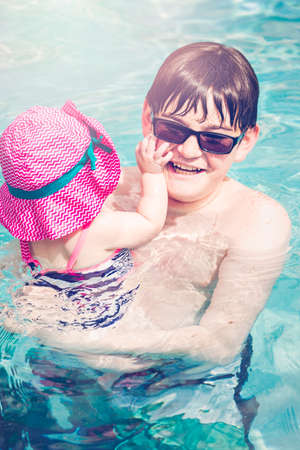 Family with cute baby girl faving fun in outdoor swimming pool on hot summer day. photo
