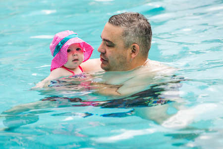 Family with cute baby girl faving fun in outdoor swimming pool on hot summer day. Stok Fotoğraf