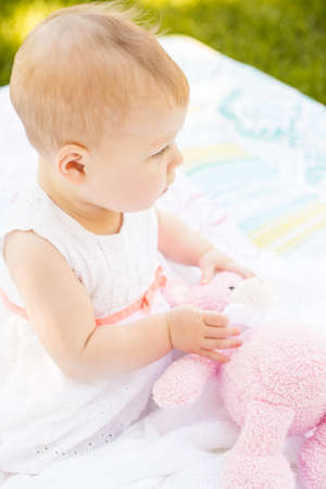 Cute baby girl playing on blanket in the park. photo