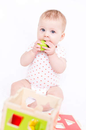 Cute baby girlplaying on a white blanket. photo