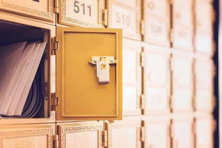 buzon de correos: Las filas de cajas de la oficina de correos de oro con una casilla de correo abierto