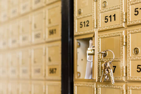 Rows of gold post office boxes with one open mail box Stock Photo - 29463249