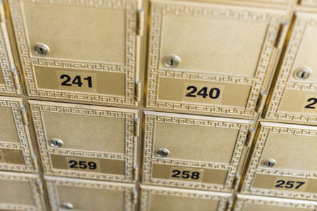 Rows of gold post office boxes with one open mail box Stock Photo - 29463252