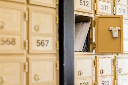 Rows of gold post office boxes with one open mail box Stock Photo - 29440740