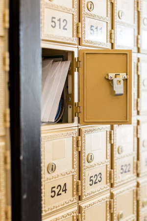 Rows of gold post office boxes with one open mail box Stock Photo - 29463262