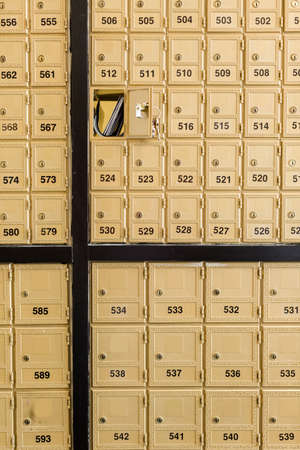 Rows of gold post office boxes with one open mail box Stock Photo - 29463271