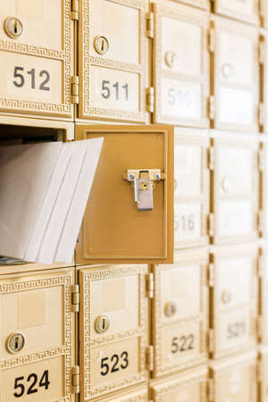 Rows of gold post office boxes with one open mail box Stock Photo - 29463272