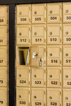 Rows of gold post office boxes with one open mail box Stock Photo - 29463275