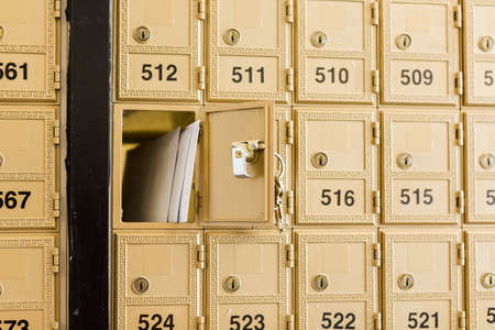 Rows of gold post office boxes with one open mail box Stock Photo - 29463277