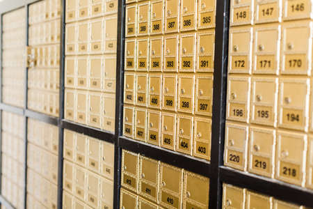 Rows of gold post office boxes with one open mail box Stock Photo - 29463408