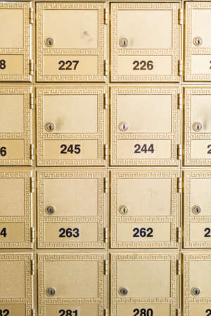 Rows of gold post office boxes with one open mail box Stock Photo - 29463378