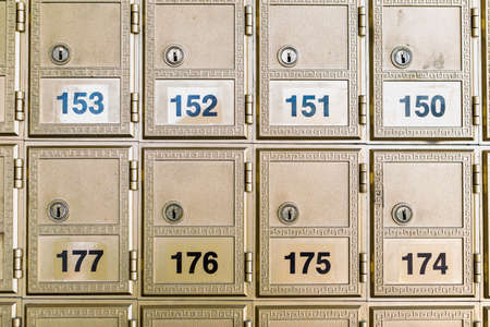 Rows of gold post office boxes with one open mail box Stock Photo - 29463379