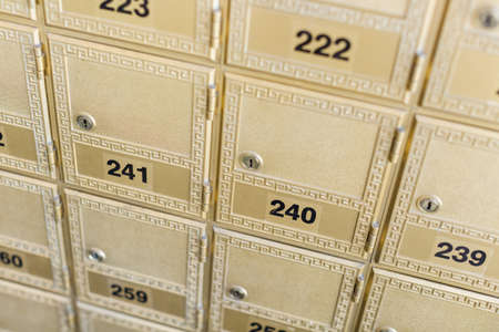 Rows of gold post office boxes with one open mail box