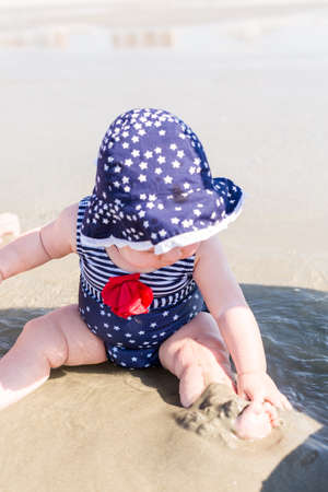 Cute baby girl playing on the beach. photo