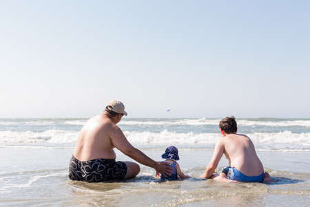 Family playing on the beach during their vacation. photo