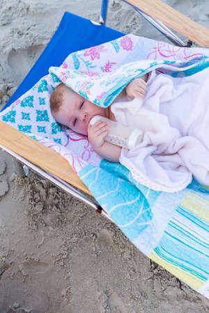 Cute baby girl resting in beach chair on the beach. photo