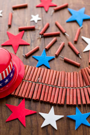 Roll of firecrackers with red, white and blue stars on wood table.