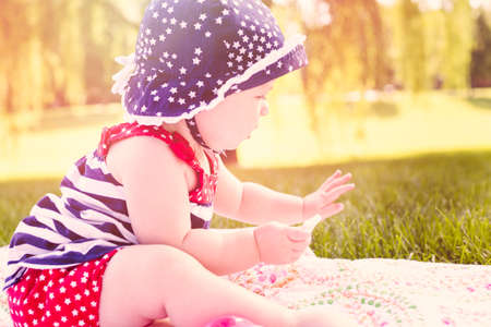 Cute baby girl celebrating 4th of July in the park. photo