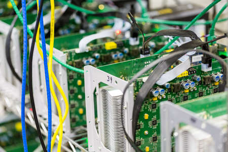 Denver, Colorado, USA-August 13, 2014. Row of bitcoin miners set up on the wired shelfs.