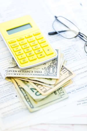 Calculating income tax return with folded cash on a table. photo