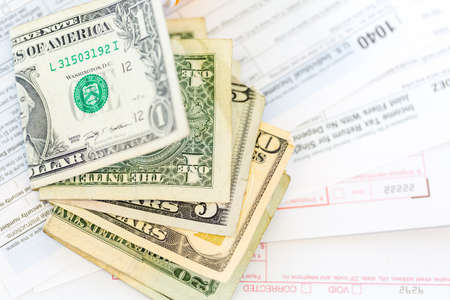 tax return: Calculating income tax return with folded cash on a table. Stock Photo