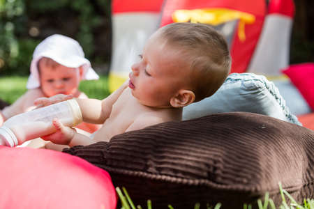 living unit: Cute babies playing on the blanket on backyard.