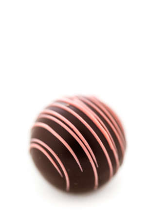 Gourmet strawberry chocolate truffle on a white background.
